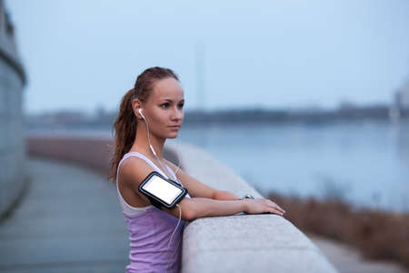 faraway: sporty woman on river bank wearing sport armband looking faraway