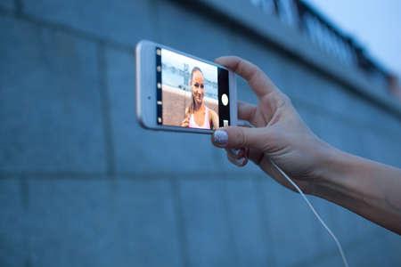 filming: closeup smartphone in sporty woman hand doing selfie