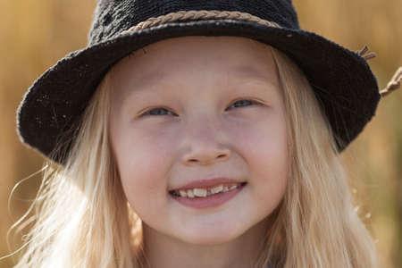niños rubios: feliz niña rubia en campo de trigo con el pelo largo, cara del retrato del primer