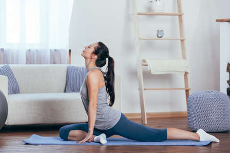 Young attractive smiling woman practicing yoga at home Stock Photo