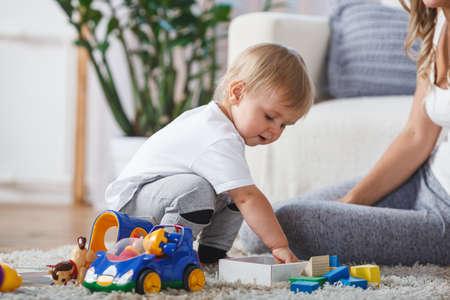 Carino ragazzo madre e figlio giocare insieme in casa a casa Archivio Fotografico - 75960123
