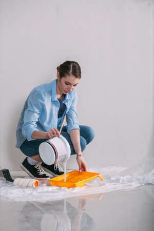 housepainter: woman sitting on the floor and mixing wall paint