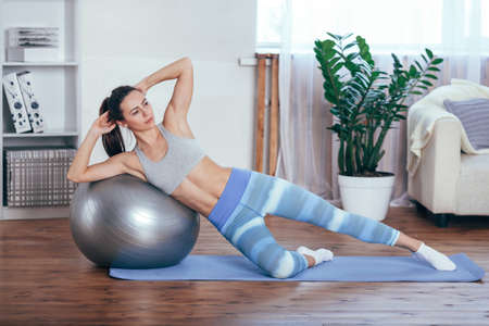 Young sportswoman doing exercises with ball on a mat at home Фото со стока - 77109691