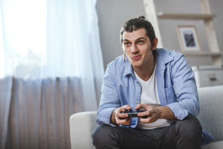 young man seated on a sofa playing video games inside his room Stock Photo