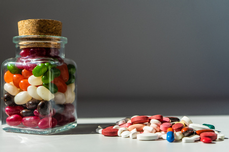 Glass jar full of candies, group of colorful pills on white table. Stock Photo - 123639018