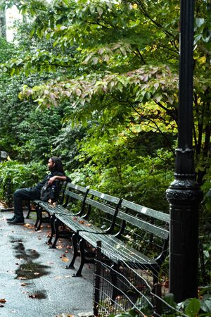 Rainy day in central park, New York, Man on wet bench looking far away