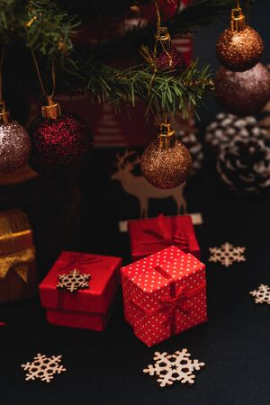 Small red gift boxes under the tree, black background, christmas decoration, christmas gifts, christmas picture for social media, empty space for text Stock Photo