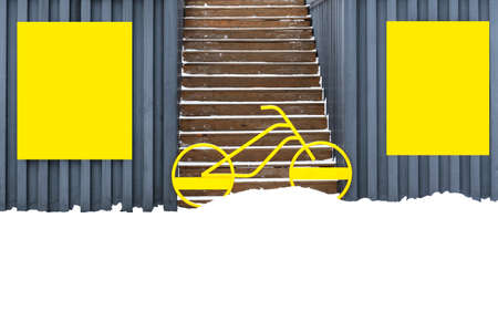 On the walls of garages hang yellow shields, between which stands a bicycle and blocks the entrance to the stairs. Banco de Imagens - 120691102