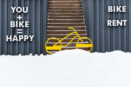 A bright yellow bicycle blocks the entrance to the stairs going up