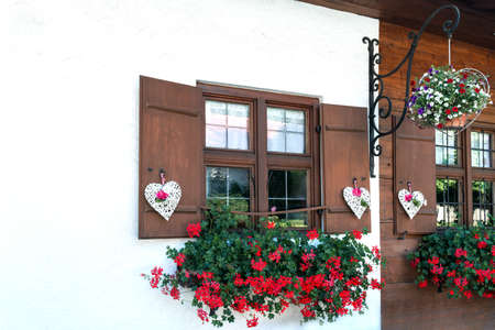 The windows of the wooden house are beautifully decorated with white hearts and flowers