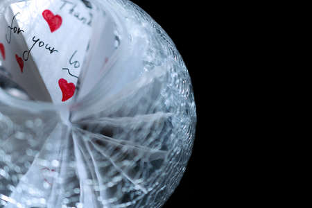 Glass ball with notes of love on a black background