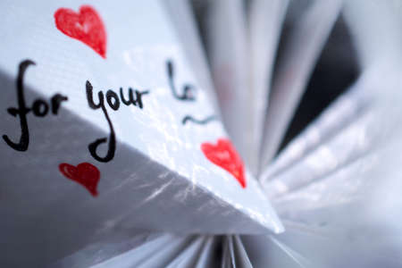 A white note with hearts and words of gratitude lies on a pile of papers 写真素材