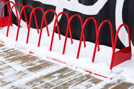 View of the red bicycle parking on the background of a metal wall and snow