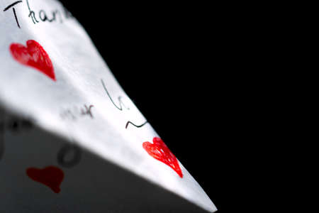 On a black background is a white note with red hearts on which the words of gratitude are written