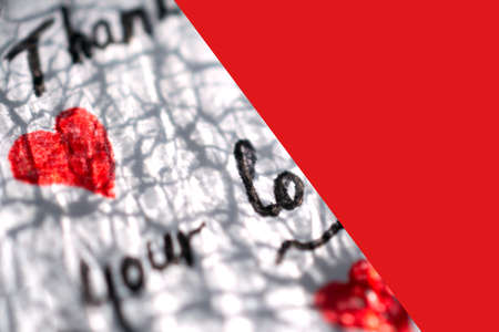Part of a white note with hearts and words of gratitude lies on a red background Reklamní fotografie