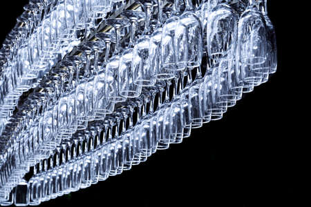 A large number of glasses in the shape of an oval hang on the holder at the bar counter on a dark background.