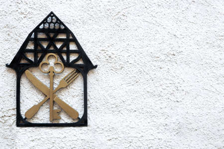 A sign on the wall with the image of the house key knife and fork.
