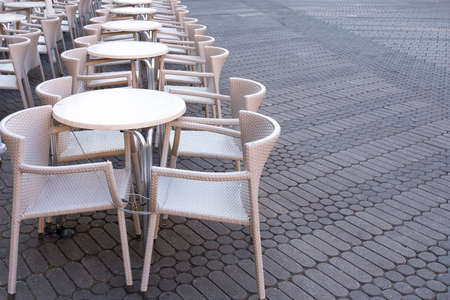 A number of empty tables with chairs are connected by a cable from theft in a cafe on the street.