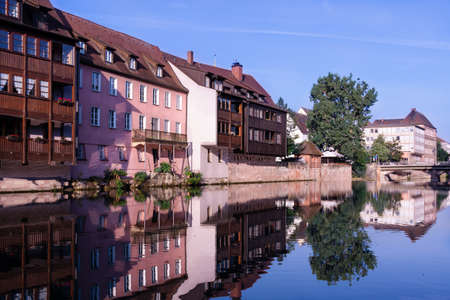 A number of houses stand on the banks of the Pegnitz River in Nuremberg Germany