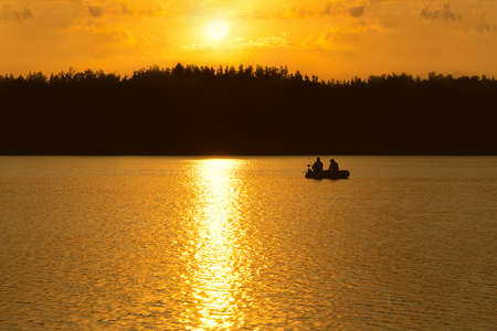 Fishermen catch fish on the lake at sunset.