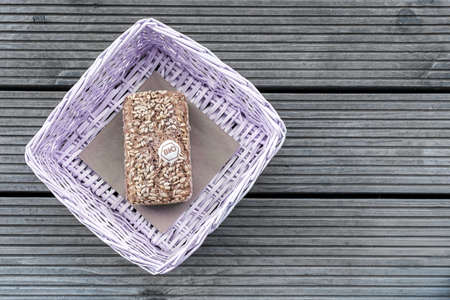 A loaf of bread lies in a lilac basket on a wooden table