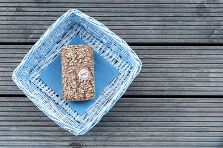 A loaf of bread lies in a blue basket on a wooden table Reklamní fotografie