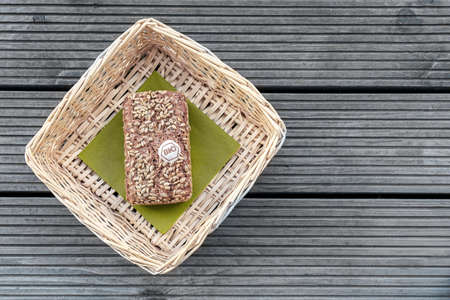 A loaf of bread lies on a green napkin in a beige basket on a wooden table