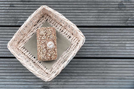 A loaf of bread lies in a beige basket on a wooden table