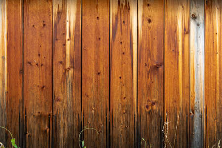 Wooden wall with a protective layer of brown paint