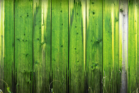 Wooden wall with a protective layer of green paint
