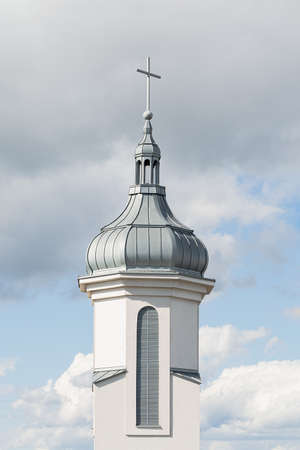 View of the dome and bell tower of a modern Catholic church against a blue sky with clouds. Concept architecture, easter, religion