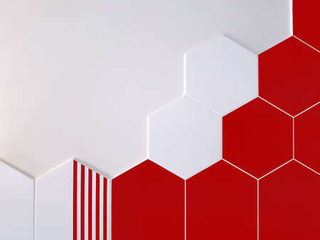 A background of bright red and white ceramic tiles in the shape of a hexagon that partially covers a white wall. Concept texture, background