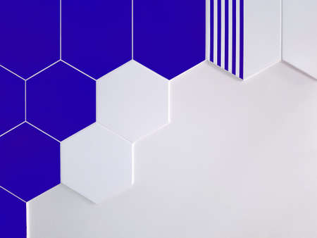 A background of bright blue and white ceramic tiles in the shape of a hexagon that partially covers a white wall. Concept texture, background