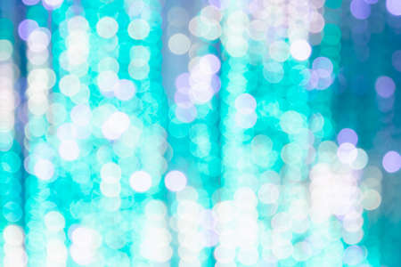 Bright background from blurry bokeh of Christmas lights in turquoise and white. Holiday concept, background, christmas