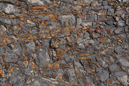 The texture of the stone surface of the mountain with minerals of different colors. Concept background, texture