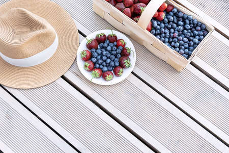 A hat and fresh strawberries and blueberries lie in a basket and on a plate on the terrace boards on the veranda. Food concept, flat layout, gardening, summer, healthy eating.