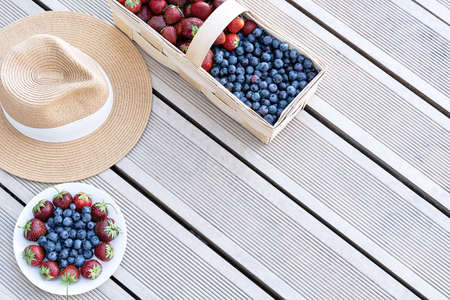A hat and fresh strawberries and blueberries lie in a basket and on a plate on the terrace boards on the veranda. Food concept, flat layout, gardening, summer, healthy eating 写真素材