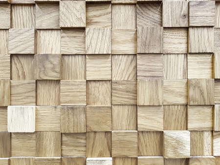 Wall with the texture of wooden cubes that bulge out in a chaotic manner