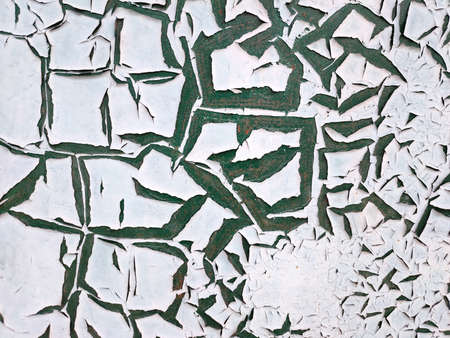 The texture of the painted wall with peeling white paint which is covered with large green cracks. Concept background, texture