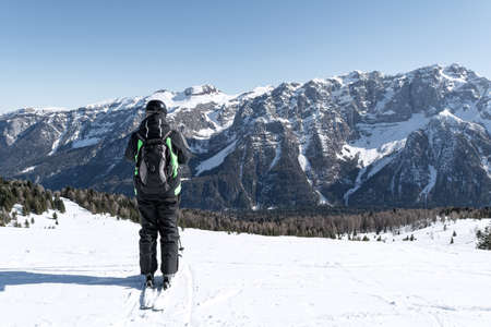 A man stands on the side of a mountain against the backdrop of the snow-capped Dolomites. Concept for sports, landscape, people