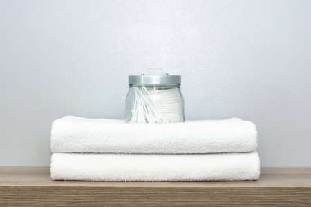 A view of a glass jar of personal hygiene items that stands on two neatly folded towels Stockfoto