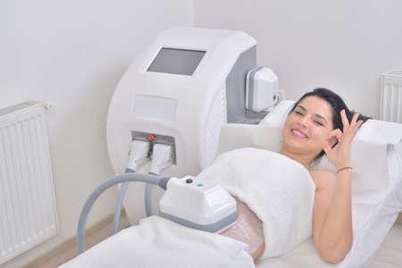 かなり若い女性プロ化粧品キャビネットの cryolipolyse 治療を得ること