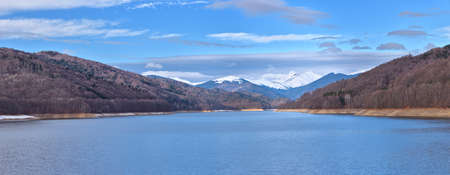 Mountain lake panorama against cloudy sky and mountains covered with snow Stock Photo