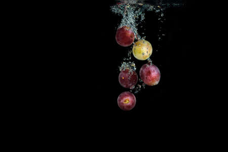 Fresh red grape in water with air bubbles water splash