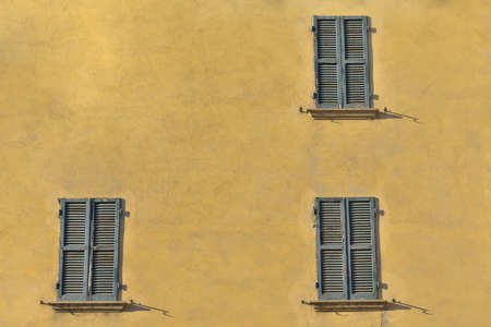 jalousie: Closed green windows on yellow wall of old house in Florence city, Italy Stock Photo