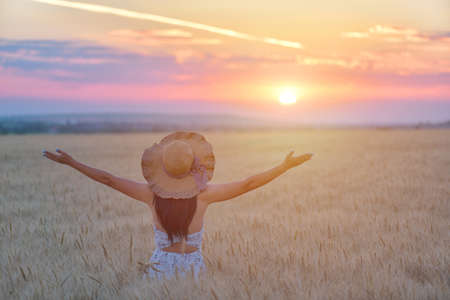 Woman feeling free, happy and loved in a beautiful natural setting at sunet Stock Photo
