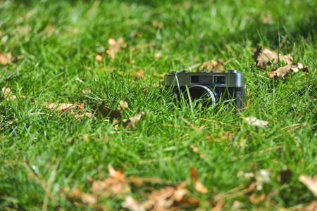 Old vintage analog rangefinder photo camera in nature autumn grass background