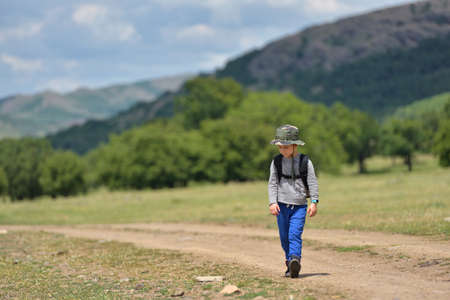 walking path: Cute child boy with backpack walking on a little path in mountains. Hiking kid Stock Photo