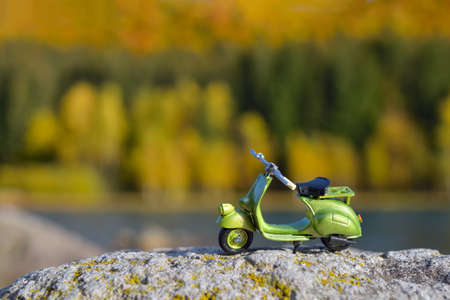 Small retro green scooter toy on a rock, autumn colors background