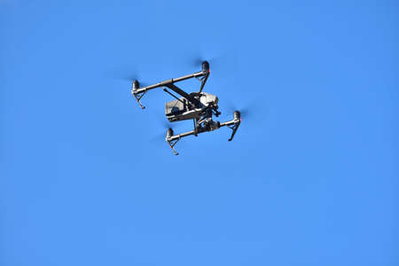 Flying drone on blue sky background